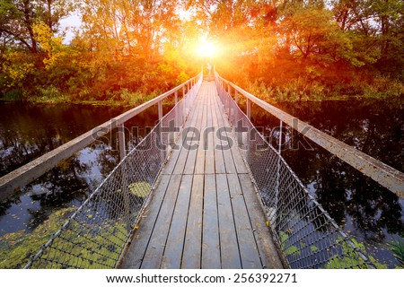 Small bridge over river in forest on sunset background - stock photo