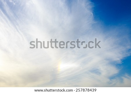 Small bright rainbow in a clouds on blue sky - stock photo