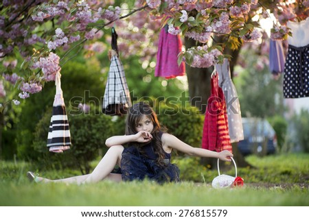 Small brunette girl with basket looking away sitting in the park among colorful baby dresses hanging in the japanese cherry blossom tree, horizontal picture - stock photo