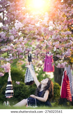 Small brunette girl with basket sitting in the garden among colorful baby dresses hanging in the japanese cherry blossom tree with hihlight throwing petals copyspace, vertical picture - stock photo