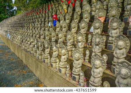 Small buddhist statues called Jizo. Usually seen as a protector of safe travel and children. Found in Japan. - stock photo