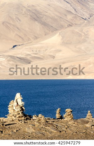 Small Buddhist stupas, collected in the form of a stack of zen stones in the lake Tso Moriri surroundings against the background of the lake and the Himalayas at the sunset (Ladakh, northern India) - stock photo