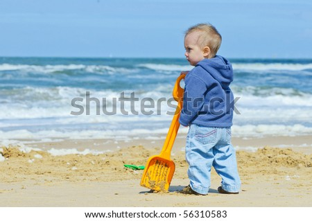Small builder. 2-year-old cute boy on the beach of the North Sea