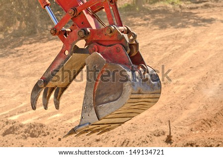 Small bulldozer moving dirt from a hillside in preparation for a new commercial construction development