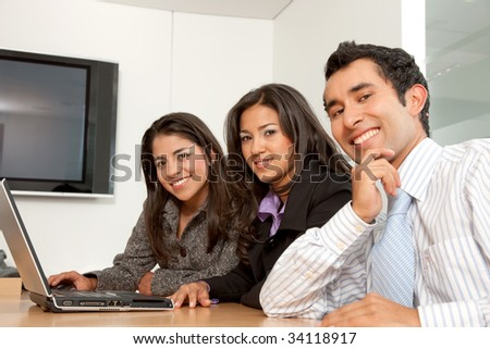 Small business group working with computer smiling - stock photo