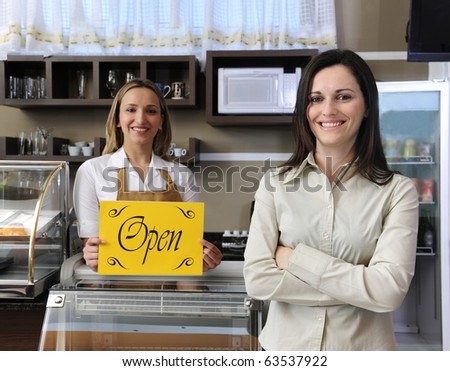 Small business: Happy owner of a cafe showing open sign - stock photo