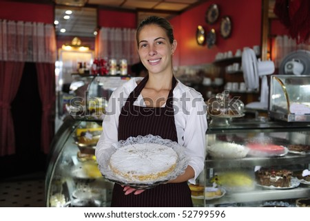 small business: happy waitress showing a tasty cake - stock photo