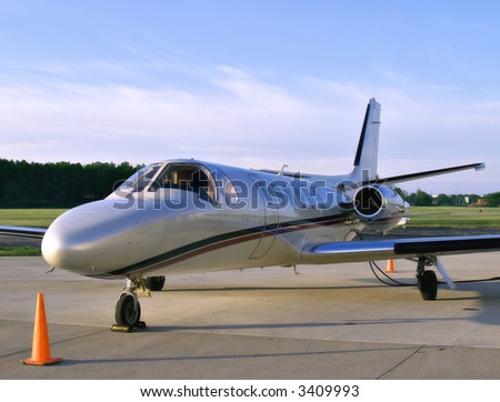 Small business jet sits on the tarmac waiting for its passengers - stock photo