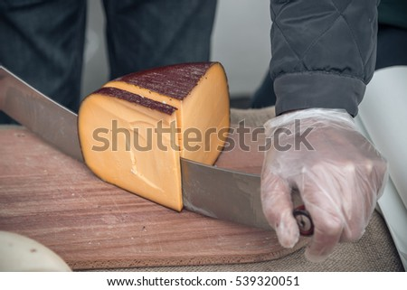 Small business owner, cutting a head of cheese using double handed cheese knife. Close up of cutting cheese on street market.