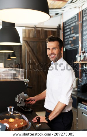 Small business owner making coffee at cafe - stock photo