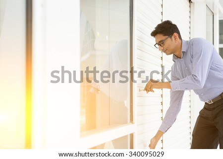 Small business owner opening his new shop in morning. Handsome Asian Indian guy. - stock photo