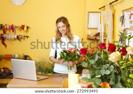 Small business owner. Portrait of mature florist standing in her small flower shop behind the laptop while preparing flowers for arranging. - stock photo