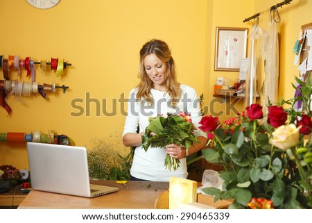 Small business owner. Portrait of mature florist woman standing at her flower shop behind the laptop while holding hands bouquet and smiling. - stock photo
