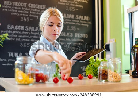 Small business owner reading the recipe on a digital tablet - stock photo