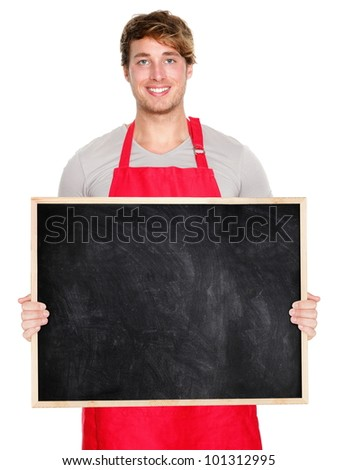 Small business owner showing blank empty blackboard sign wearing apron. Handsome young shop owner man isolated on white background smiling happy. - stock photo