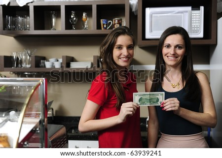 Small business: Owners of a cafe holding cash and smiling - stock photo