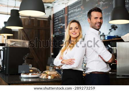 Small business partners standing together at their coffee shop, cafe - stock photo