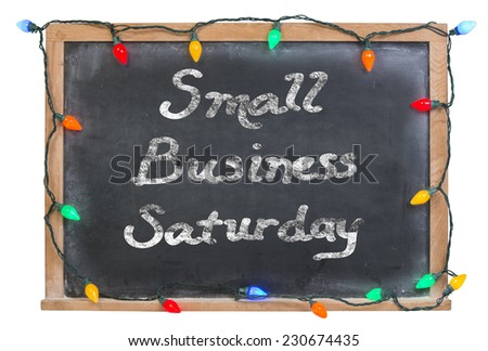 Small business saturday written in white chalk on a black chalkboard surrounded with colored lights and isolated on white - stock photo