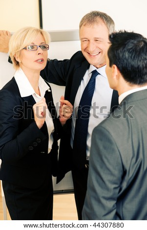 Small business team group standing in the office in front of a whiteboard discussing a project very energetically - stock photo