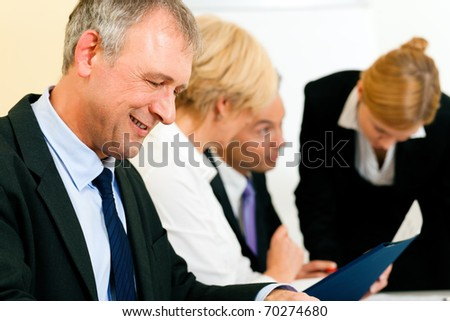 Small business team in the office in front of a whiteboard discussing a project and some documents - stock photo