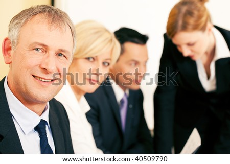 Small business team working in the office, one senior businessman in front looking at the viewer (selective focus) - stock photo