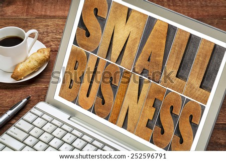 small business text in letterpress wood type printing blocks on a laptop with a cup of coffee - stock photo
