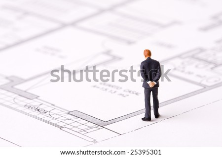 small businessman examining an architech blueprint (selective focus) - stock photo