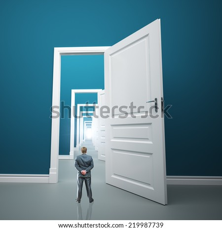 Small businessman is standing in front of long way of opened doors - stock photo
