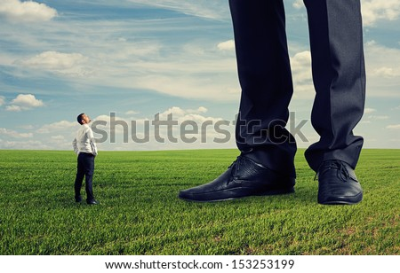 small businessman looking at his big boss. photo on green field - stock photo