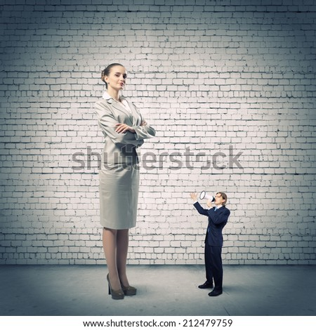Small businessman screaming in megaphone on woman colleague - stock photo