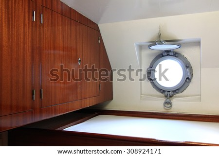 small cabin with porthole on a ship - stock photo
