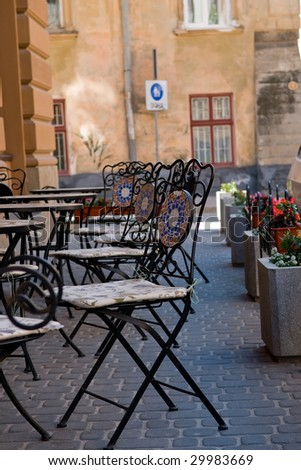 Small cafe in the street an old city. Tables and beautiful chairs on sidewalk. - stock photo