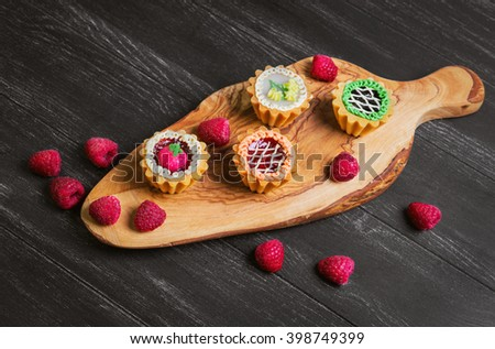 Small cakes petit fours in the form of baskets with cream and jam on a wooden plank from a tree of olive, worn on a dark black background in rustic style, top view - stock photo