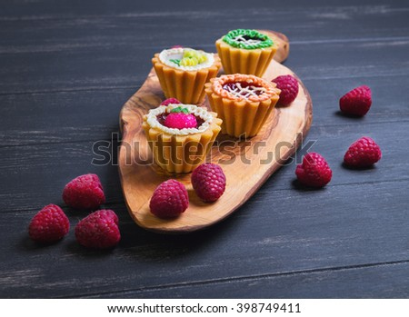 Small cakes petit fours in the form of baskets with cream and jam on a wooden plank from a tree of olive, worn on a dark black background in rustic style - stock photo