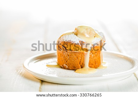Small cakes with apple powdered with sugar and coated with vanilla sauce on white wood table - stock photo