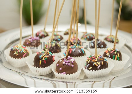 Small cakes with different stuffing. Many tiny cakes with strawberry, coffee, whipped cream, jelly and mint - stock photo