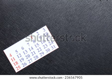Small calendar put on black color leather background represent the new year.