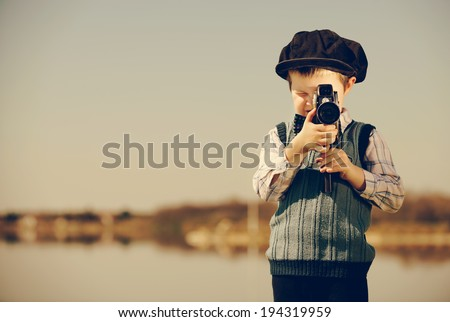small cameraman captures nature. vintage- look / retro photographer - stock photo