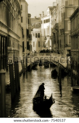 Small canal and gondola among the houses in Venice, Italy (sepia toned). - stock photo