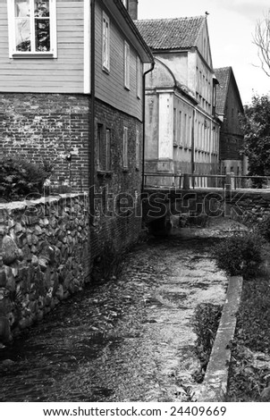 Small canal between houses in old town. Black and white