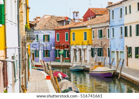 Small canal lined with colorful houses on the island near Venice in Italy. The name of the island is Burano. All potential trademarks are removed.