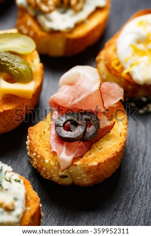 Small canape, crostini  with grilled baguette with the addition of ham and olives on  black background. Delicious appetizer - stock photo