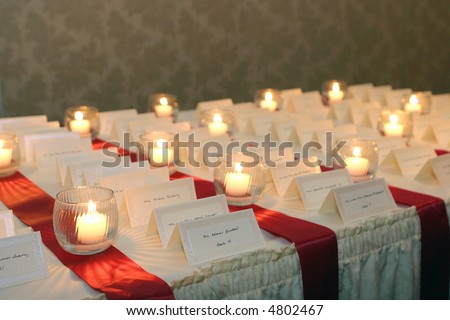 small candles lighting placecards for guests at a wedding reception - stock photo