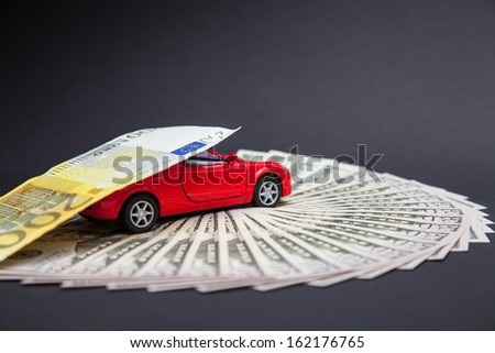 Small car carrying an euro banknote, grey background - stock photo