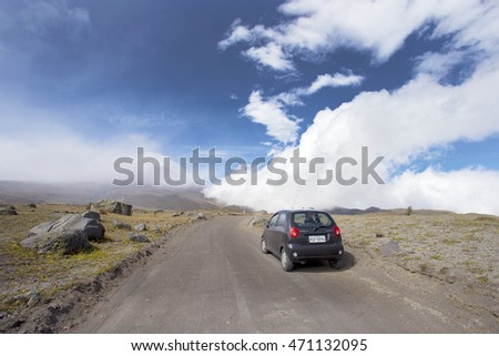 SMALL CAR DRIVING TO COTOPAXI VOLCANO, ECUADOR - JULY 20, 2016: Driving small black car in Cotopaxi NP, Ecuador