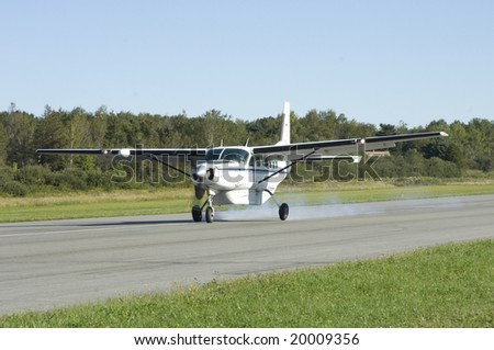 Small cargo plane landing at Owl's Head airport, Maine - stock photo