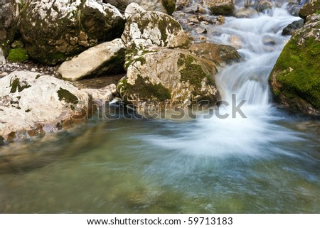 Small cascade and flowing water and moss on rocks - stock photo