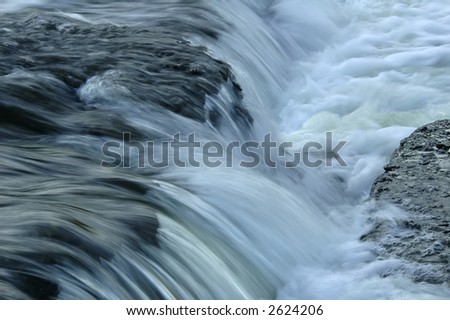 Small cascade of water falling over rocks in a rain swollen stream. - stock photo