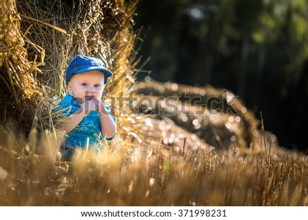 Small caucasian boy sitting and playing outdoor on stubble field. - stock photo