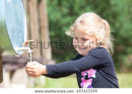 Small Caucasian child washing hand in water dispenser outdoor - stock photo